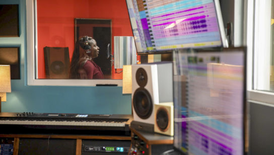 a female student records vocals in the music studio on campus