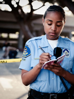 an officer stands outside of the police tape and writes notes in a notepad