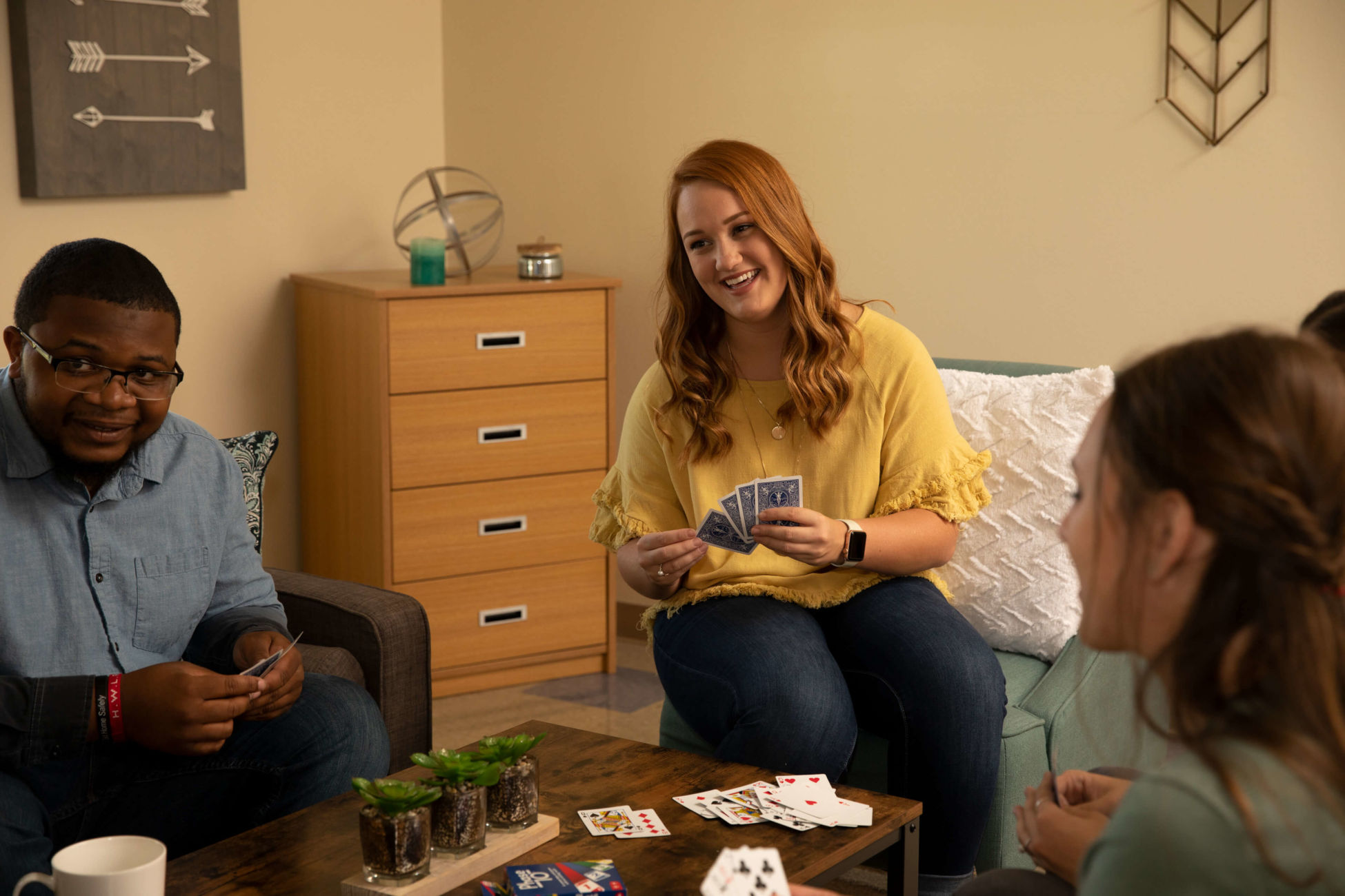 several students playing cards in a dorm room