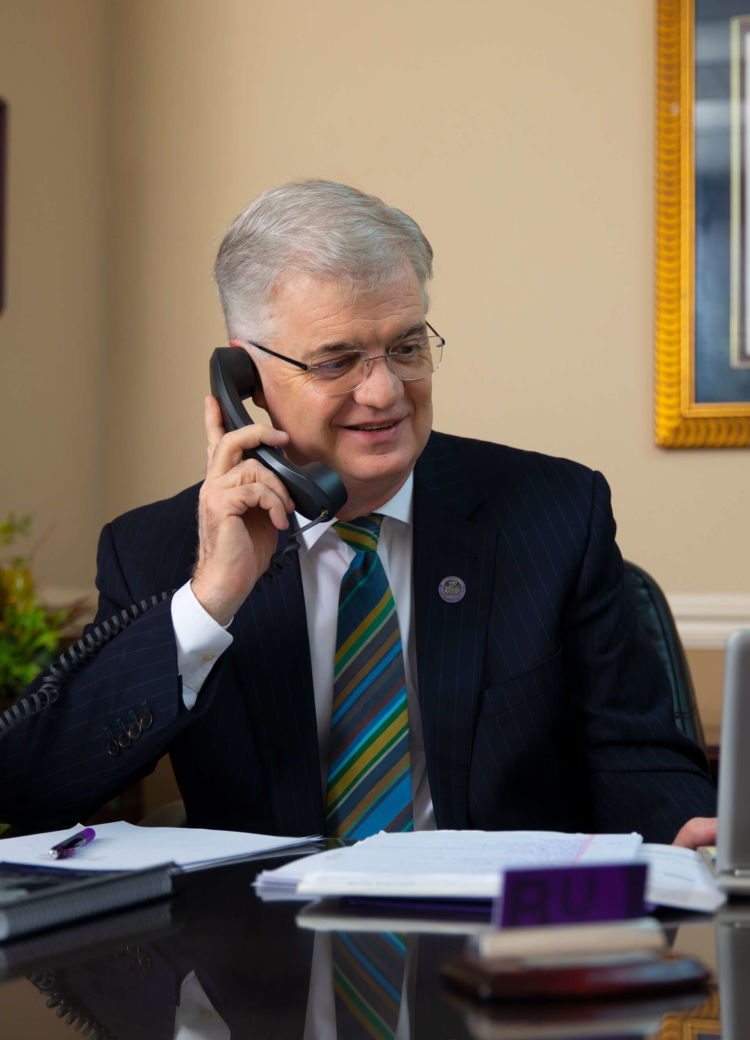 President Butler speaks on the phone at his desk