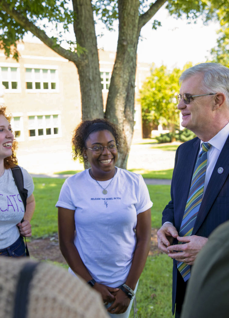 President Butler speaks with students outside