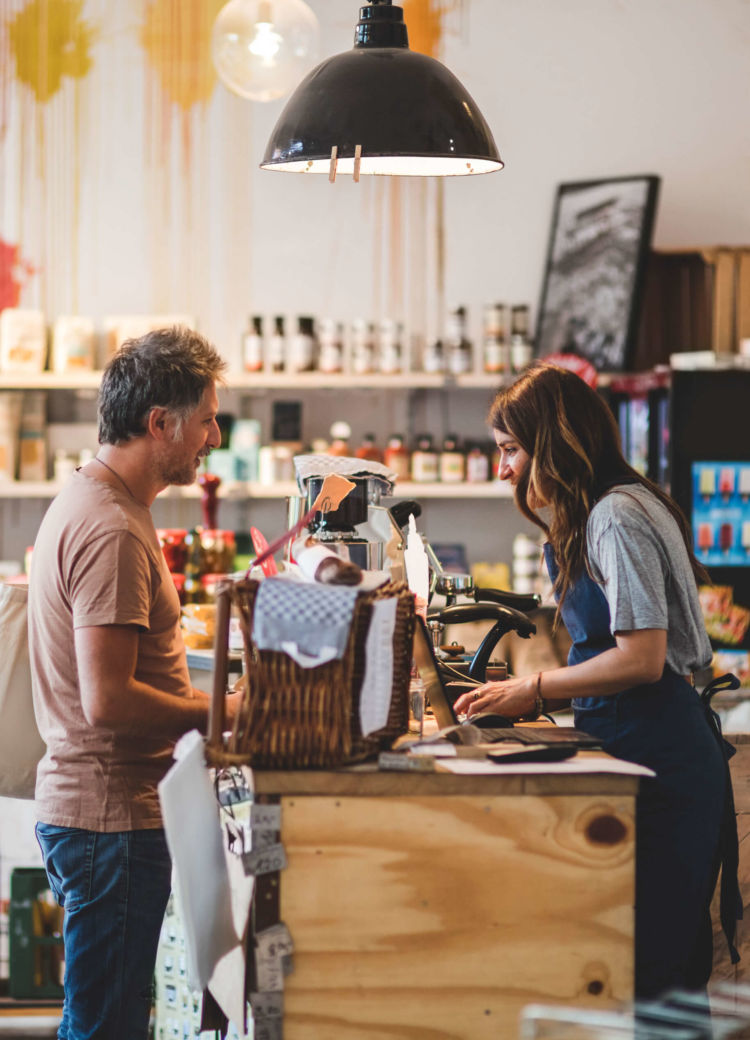 a storeowner greets a customer at the point of sale