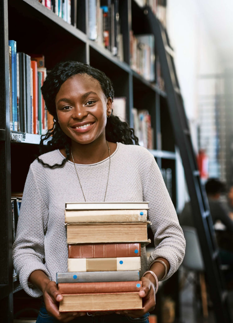 a female student holds a stack of books in the library