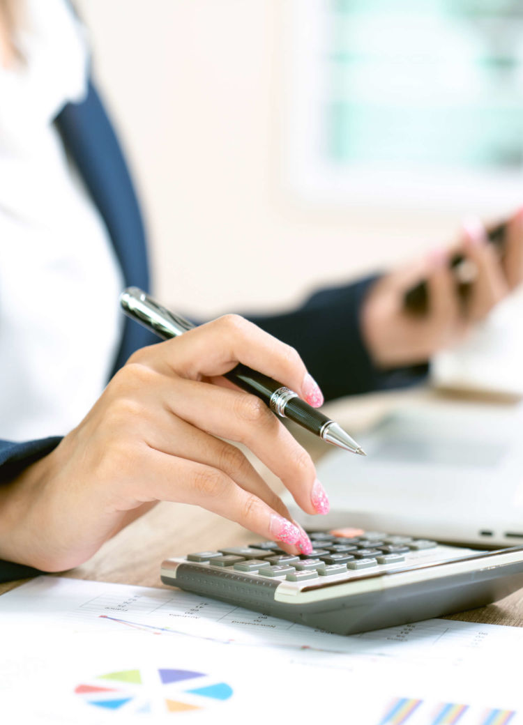 a female business admin enters some accounting figures into her calculator