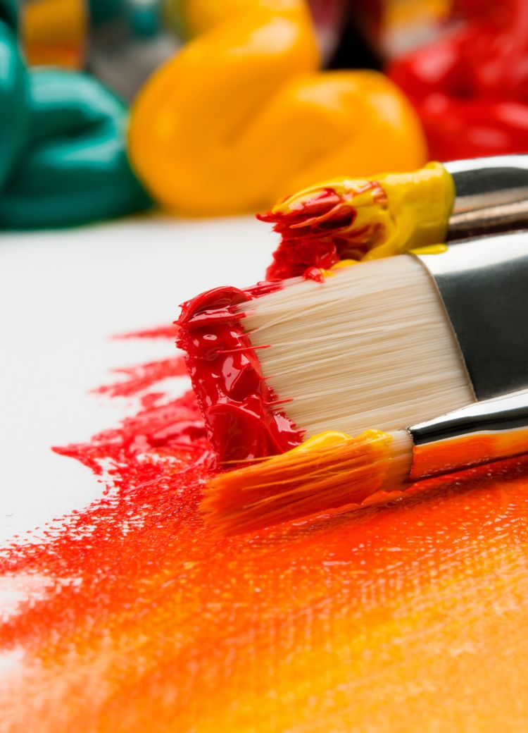 paint brushes on a vibrantly painted canvas