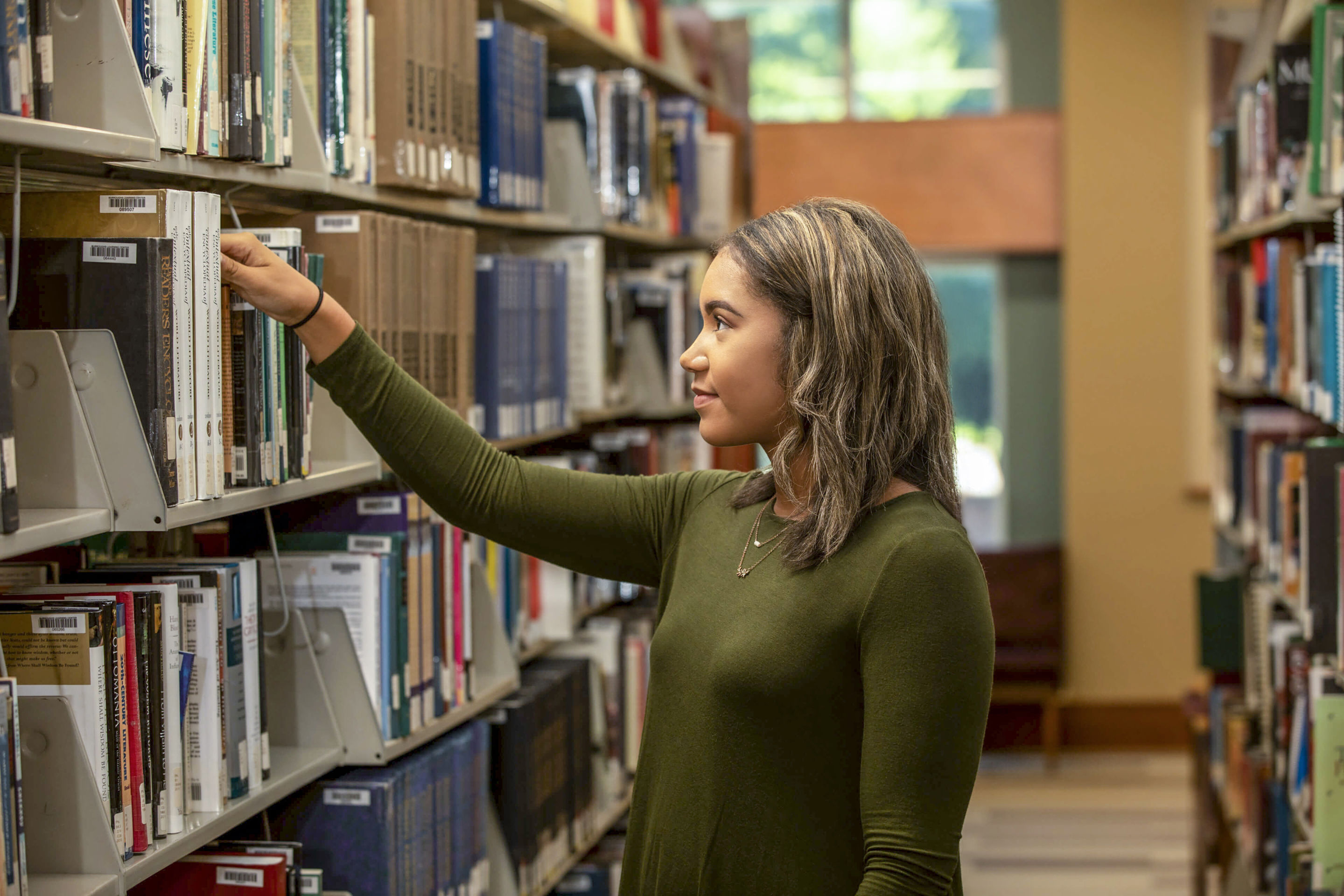 a female student searches for a library book