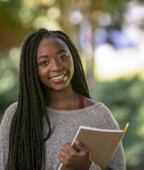 an outdoor portrait of a female student holding a notebook