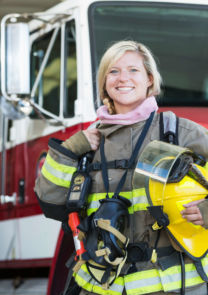 a fire and rescue servicewoman stands in full gear in front of her engine