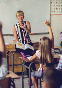 a teacher gets ready to call on a class of children with raised hands