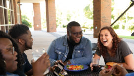 a group of students eat lunch on the patio