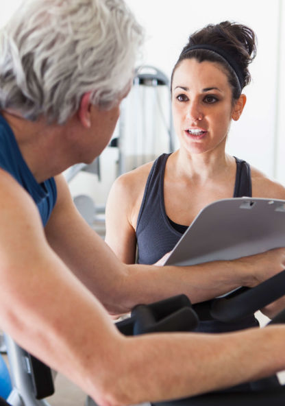 a fitness trainer works with a middle-aged man on an exercise bike