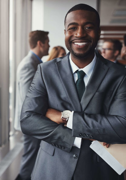 a man in a suit smiles for his portrait with a folder