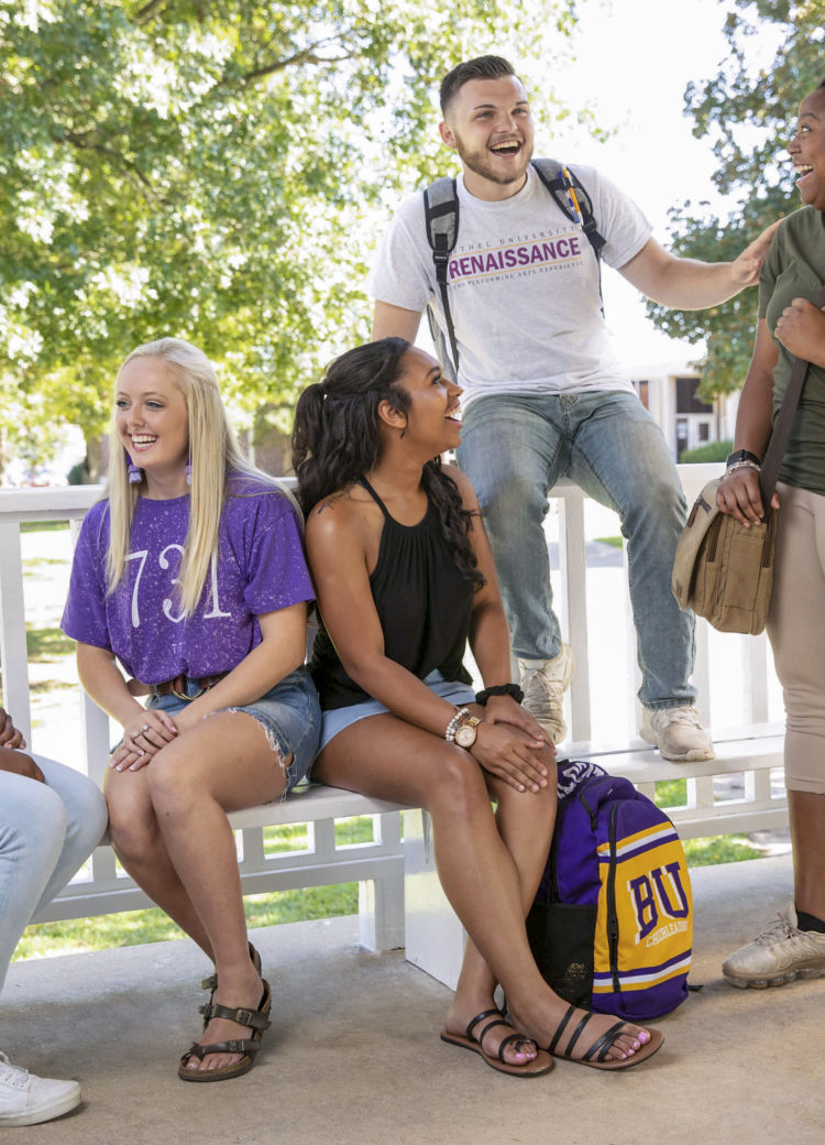 students laugh together under the gazebo on campus
