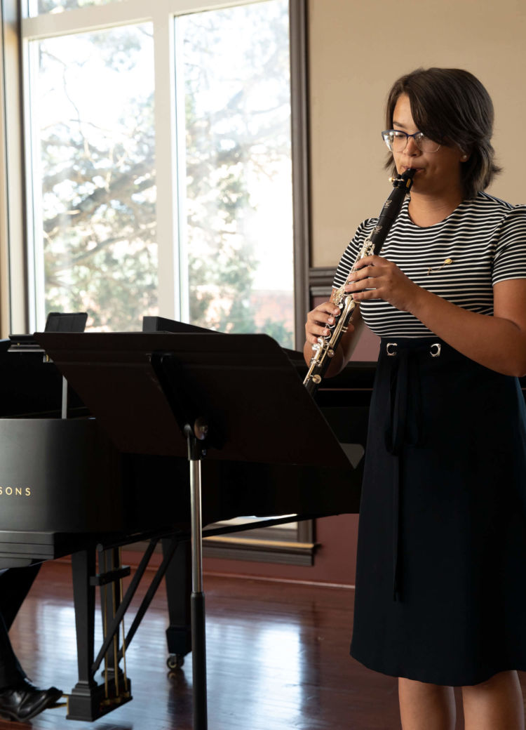 A woman playing the clarinet at a music recital